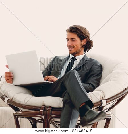 modern businessman with a laptop sitting in a stylish comfortable chair
