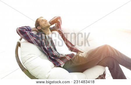 serious guy rests sitting and dreaming in a large comfortable ch
