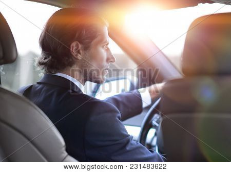 successful man sitting behind the wheel of a car