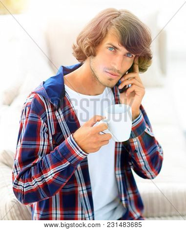 beautiful guy with a cup sits in front of a laptop.