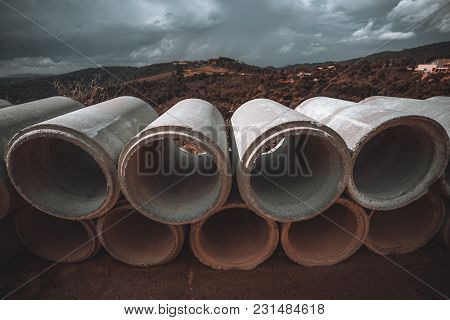 Wide-angle View Of The Two Rows Of The Cement Or Concrete Soil-pipes Laying On The Ground, Used For