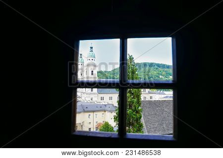 View Through Window Over Buildings And Church Dome To Green Hills Beyond From Catacombs In Salzburg,