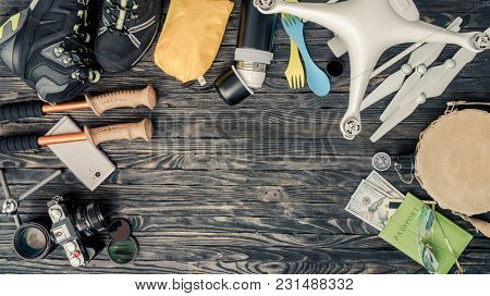 Top view of traveling items on wooden background. Packing for active vacations. Journey preparation. Copy space