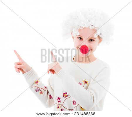Young teenage girl in white wig and red nose pointing up with fingers while looking at camera isolated on white background