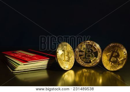 Bitcoin Three Coins Closeup On Reflective Surface With Dark Blue Background And Stack Of Credit Card
