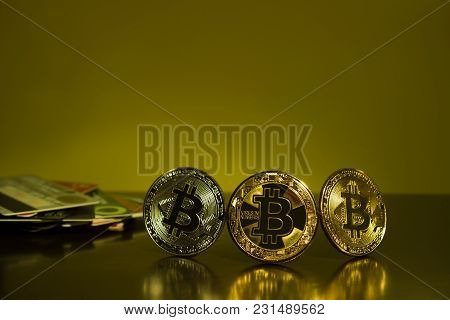 Bitcoin Three Coins Closeup On Reflective Surface With Dark Yellow Background And A Credit Card In T