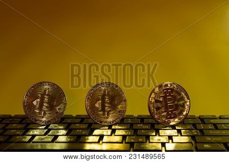 Bitcoin On Black Keyboard Three Coins Of Gold Color On A Yellow Background Free Space