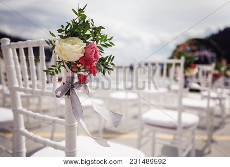 Pink Bouquets Tied With Ropes Which Hang From The White Chairs