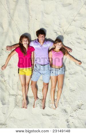 Above angle of happy teenage friends lying on sandy beach