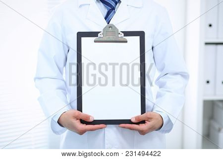 Unknown Male Doctor Standing Straight While Holding Medical Clipboard With Blank White Paper. Medici