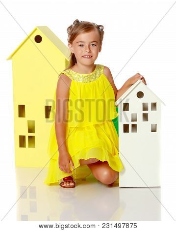 A Cute Little Girl Is Playing With Wooden Houses. The Concept Of Family Happiness, Play, Creative De