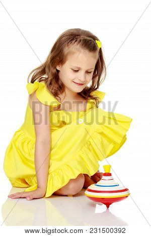 Little Girl Playing With A Whirligig. Isolated On White Background.