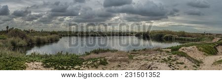 Panoramic Scene Of Rain Clouds Beginning To Form Over Reflective Water Of Pond Estuary Surrounded By