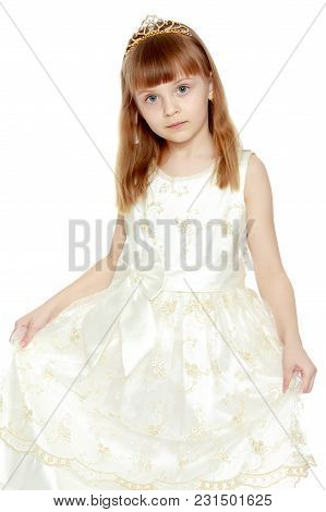 Beautiful Little Blonde Girl With Long Blond Hair And A Short Bangs. In A White Ball Dress.the Girl