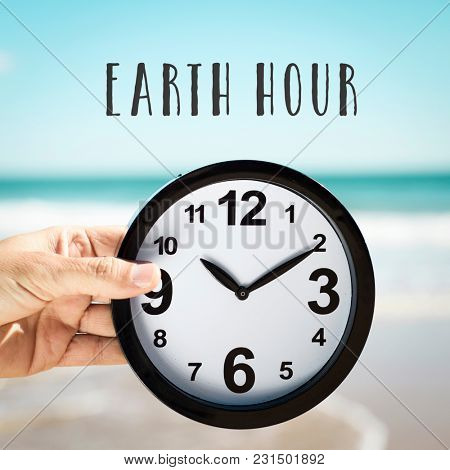 closeup of a young caucasian man holding a clock on the beach in front of the sea and the text earth hour