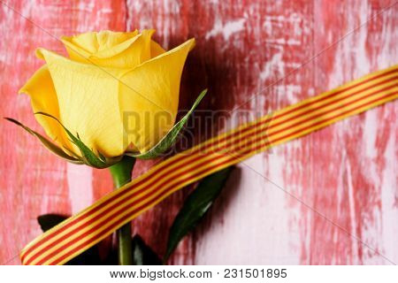 a yellow rose and a catalan flag on a rustic wooden surface for Sant Jordi, the Catalan name for Saint Georges Day, when it is tradition to give roses to women in Catalonia, Spain