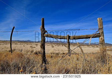 Corner Post With A Barbed Wire Fence On Ranch Land In A Desert Ranch Surrounded By A Mountain Range.