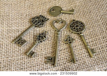 Six Antiquarian Bronze Keys On Burlap. Decor. Vintage. Indoors. Horizontal Format. Color. Photo.