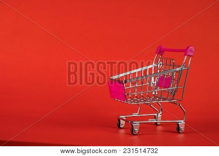Shopping Cart Or Supermarket Trolley On Red Background, Business Finance Shopping Concept.