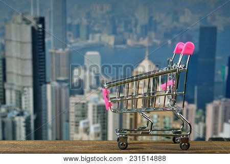 Shopping Cart Or Supermarket Trolley On Top Wooden Working Table With City City And Office Building