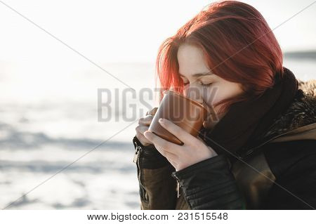 Young Woman Drinking Hot Beverage Outdoors. Good Light In The Beginning Of Spring.
