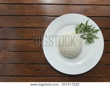 Top View Shot Of Plain Thai Rice On White Plate Decorated With Green Leaf Herb Put On Brown Wooden T