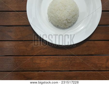 Cropped Shot Of Plain Thai Rice On White Plate Put On Brown Wooden Table With Copy Space At The Bott