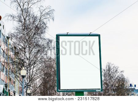 Blank Billboard On The Street On The Background Trees And Sky, Winter Urban Landscape, Mock Up