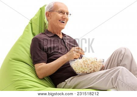 Senior seated on a green beanbag eating popcorn isolated on white background