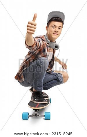 Teenager with a longboard making a thumb up sign isolated on white background