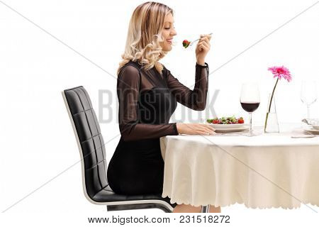 Young woman seated at a restaurant table eating a salad isolated on white background