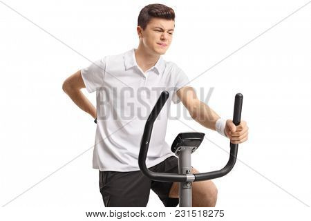 Teenager riding an exercise bike and experiencing back pain isolated on white background