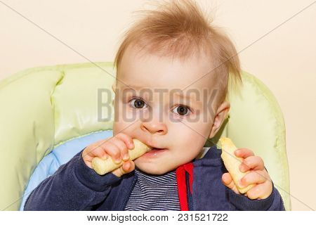 Little Baby Boy Holding And Eating Delicious Corn Snacks, Concept Of Dessert For Kids