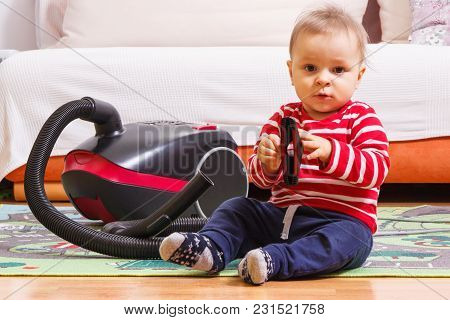 Happy Little Baby Boy Sitting On Carpet And Playing With Brush Of Vacuum Cleaner