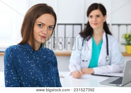 Doctor And Patient Having A Talk While Sitting At The Desk. Focus On Young Beautiful Woman Looking A