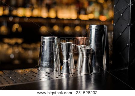 Set Of Bar Equipment Arranged On The Bar Counter Against The Blurred Background Of Bar