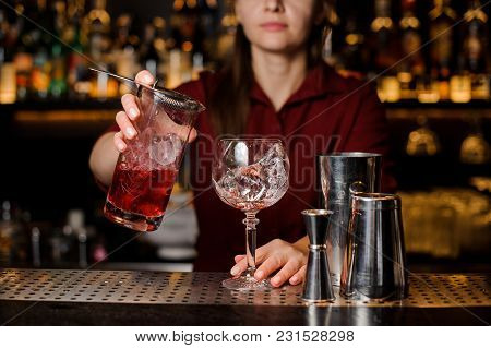 Female Barman Pouring Fresh And Sweet Red Alcoholic Drink Into A Cocktail Glass With Ice Cube