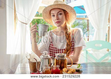 Woman In Hat Drinking Tea. Tea Pot, Homemade Honey, Jam, Muffins On Table