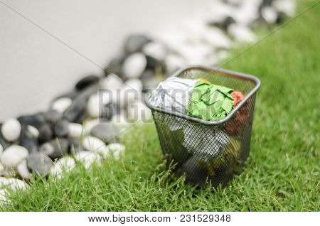 Colourful Waste Paper On Garbage Can. Surrounding By Green Grass, Black And White Decoration Rock