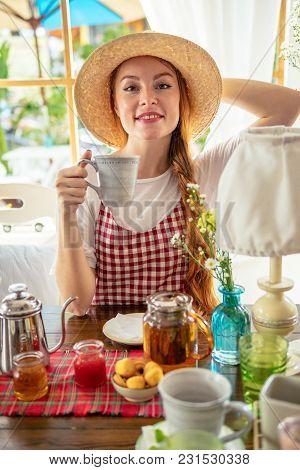 Happy Woman In Hat Drinking Tea. Tea Pot, Homemade Honey, Jam, Muffins On Table