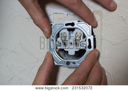 An Electrician Installs An Electrical Outlet In His Room With His Hands