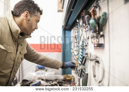 Mechanic Picking Up A Tool Box Key In The Mechanic Workshop
