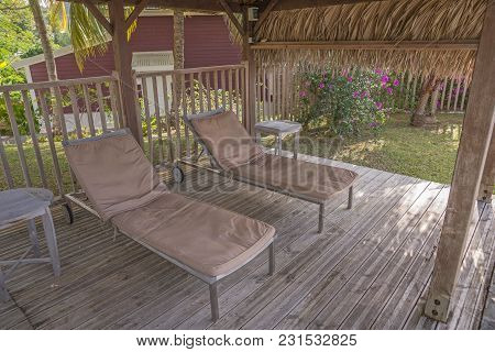 Two Empty Sunbeds In The Shade On A Wooden Platform
