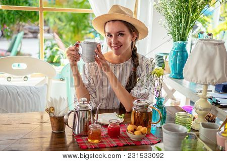 Village Girl In Hat Drinking Tea. Tea Pot, Homemade Honey, Jam, Cupcakes On Table
