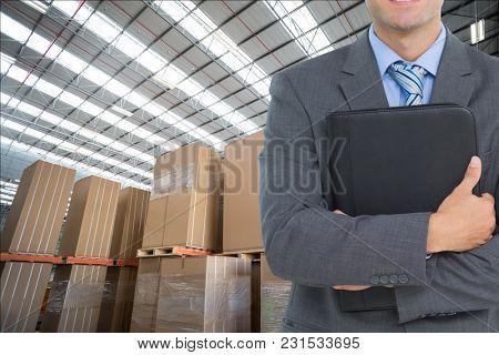 Digital composite of man in suit in warehouse