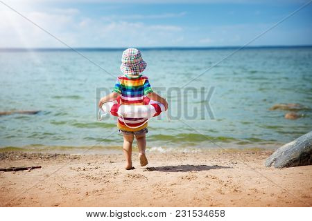 Two Years Old Boy Playing At The Beach In Hat. Child With A Lifebuoy At Sea In Summer