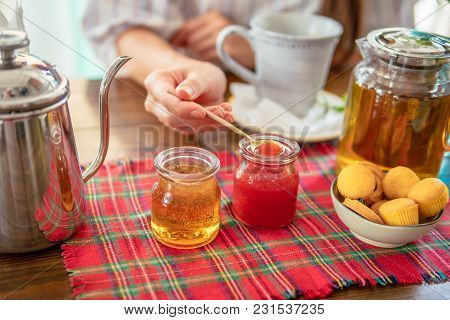 Woman Eating Homemade Strawberry Jam. Tea Pot, Honey, Small Muffins On Table