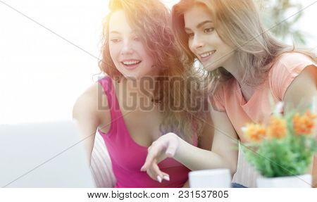 two young women discuss the video with laptop sitting at a coffe