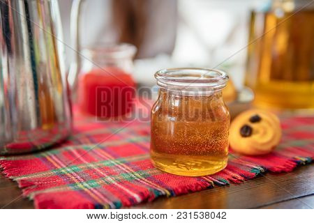 Jar Of Homemade Honey On Table. Strawberry Jam, Tea Pot And Cookies On Background.