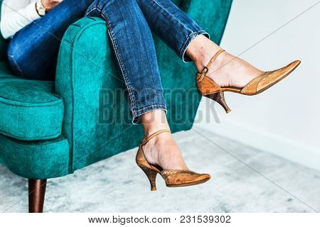 Closeup pair of feminie legs on the sofa wearing heels